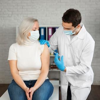 Paciente de tiro medio recibiendo una inyección