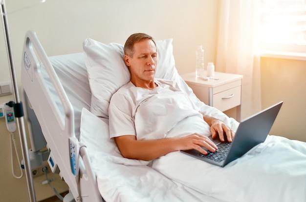 Paciente varón caucásico maduro usando la computadora portátil en la cama en el hospital. trabajando incluso estando enfermo y en el hospital.