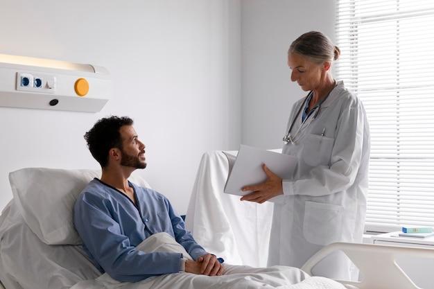 Paciente varón enfermo en la cama hablando con una enfermera