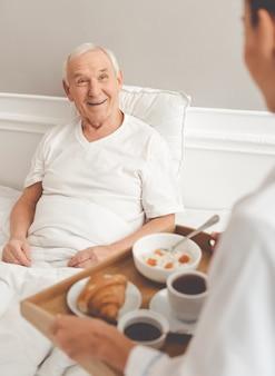 Paciente viejo guapo está recibiendo su comida de la enfermera.