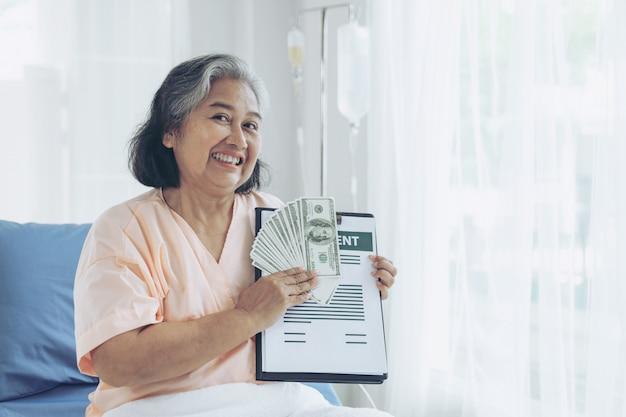 Pacientes de edad avanzada mujer lesionada en la cama del paciente en el hospital con billetes de un dólar estadounidense se siente feliz de obtener dinero del seguro de las compañías de seguros