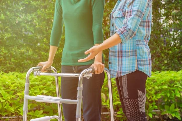 Las pacientes femeninas caminan con walker, y el fisioterapeuta ayuda y asesora.