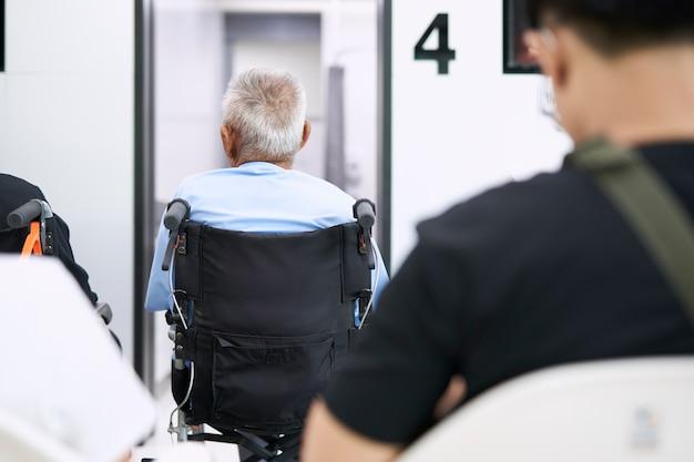 Pacientes mayores sentados en silla de ruedas mientras esperan que un médico los trate.