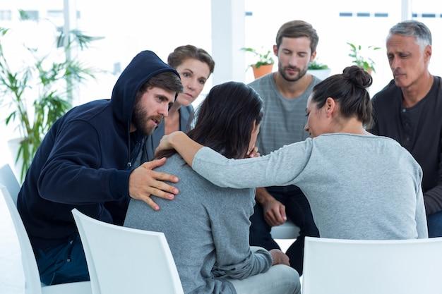 Pacientes preocupados consolando a otro en grupo de rehabilitación