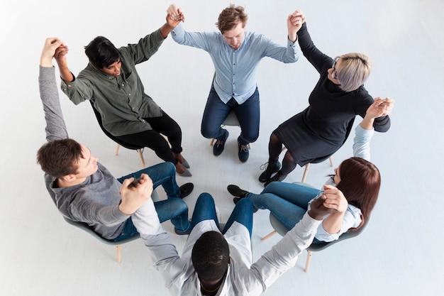 Pacientes de rehabilitación de pie en círculo y levantando las manos.