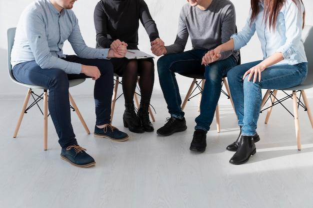 Pacientes de rehabilitación sentados en sillas y tomados de la mano