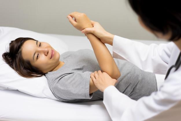 Pacientes de sexo femenino acuden a ver a un médico para controlar el dolor de codo.