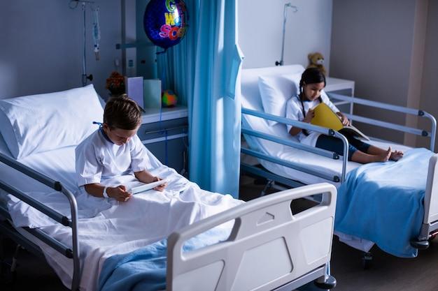 Pacientes con tableta digital y libro sentado en la cama
