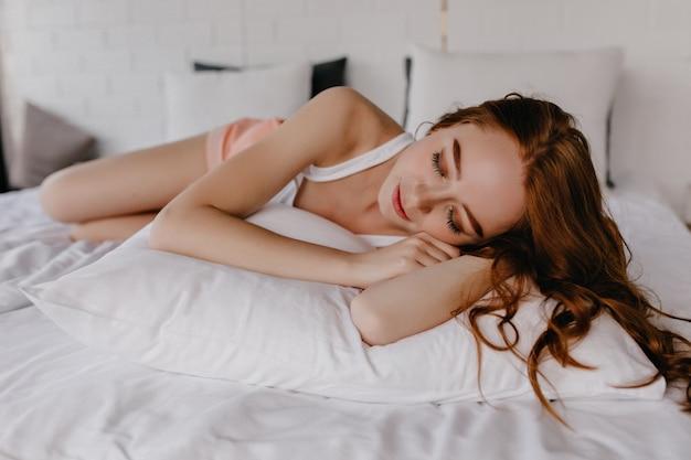 Pacífica chica pelirroja en camiseta blanca durmiendo en casa. encantadora dama caucásica descansando en el dormitorio.