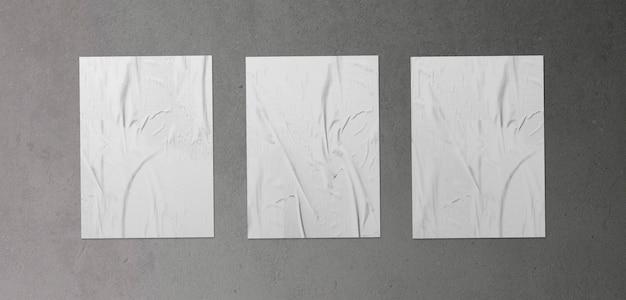 Pack de tres carteles arrugados sobre superficie de hormigón