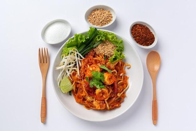Pad thai de camarones sobre fondo blanco.