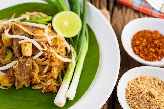 Pad thai en un plato blanco con limón, huevos y condimentos en una mesa de madera.