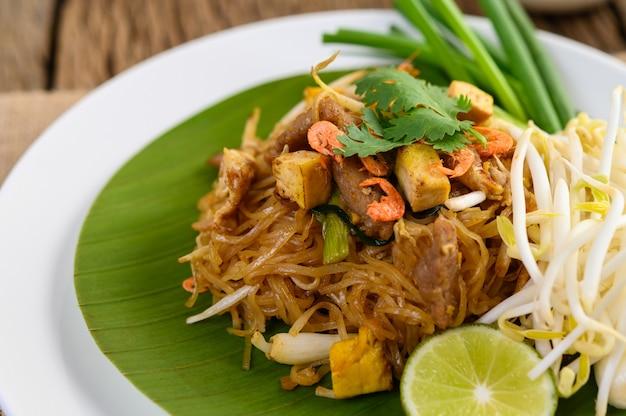 Pad thai en un plato blanco con limón sobre una mesa de madera