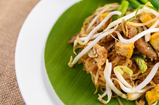 Pad thai en un plato blanco sobre una mesa de madera