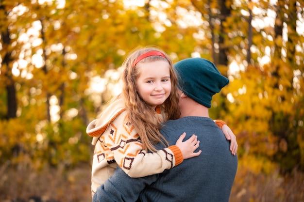Padre abraza con hija sobre fondo otoñal borroso