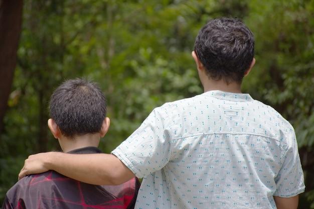 Padre abraza a su hijo y habla con gusto.