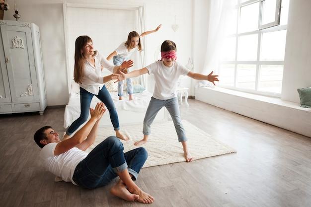 Padre acostado en el piso mientras la familia juega ciego en casa