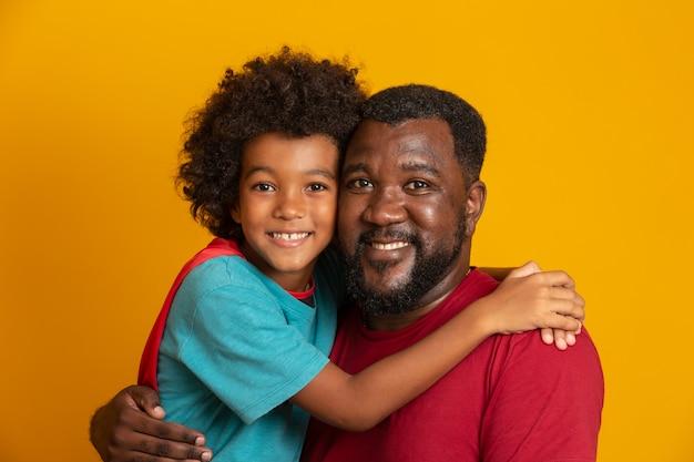 Padre africano e hijo jugando superhéroe en el día. gente divirtiéndose pared amarilla. concepto de familia amigable.