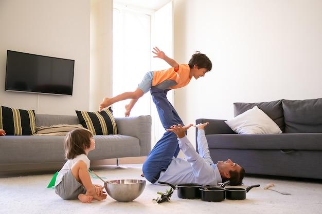 Padre alegre con hijo en las piernas y acostado sobre una alfombra. feliz niño caucásico volando en la sala de estar con la ayuda de papá. chico lindo sentado en el suelo cerca de tazón de fuente y sartenes. concepto de infancia y fin de semana.