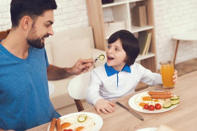 Padre está alimentando a un hijo un desayuno en la cocina.