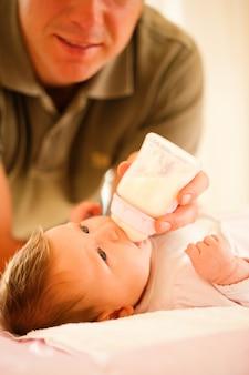 Padre está alimentando a su bebé con un biberón; escena muy tranquila