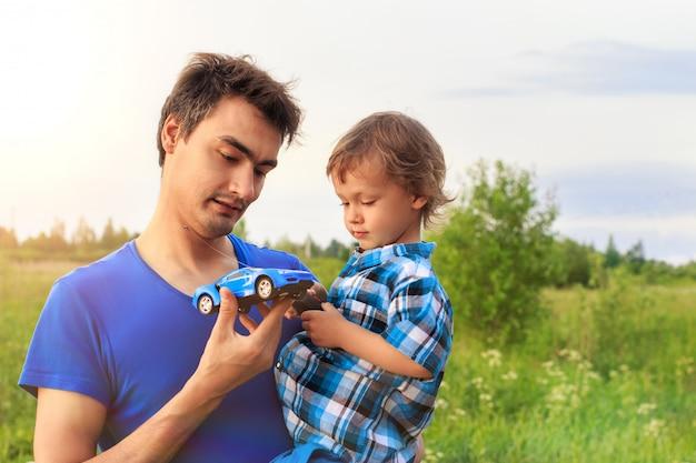 Padre amoroso con su pequeño hijo jugando al aire libre con un carro de juguete controlado por radio