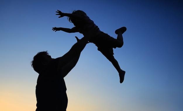 Padre amoroso y su pequeño hijo que tienen ventilador juntos al aire libre