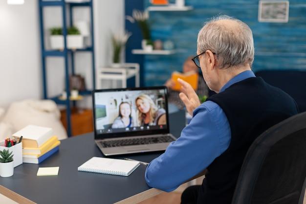 Padre anciano greenting hija durante la videoconferencia en la computadora portátil