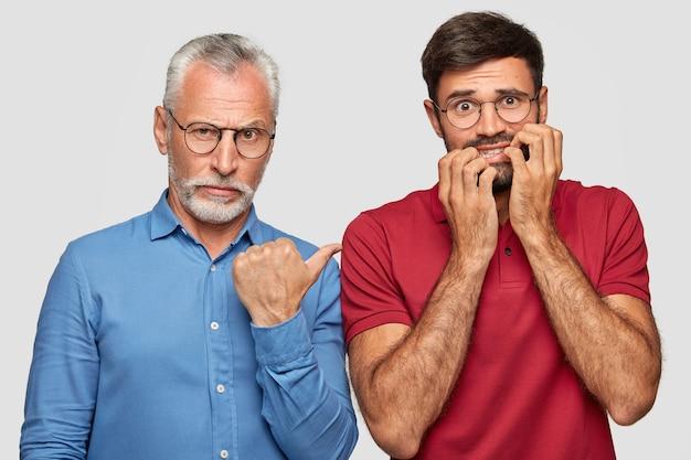 Padre ansioso nervioso e hijo adulto joven posando contra la pared blanca