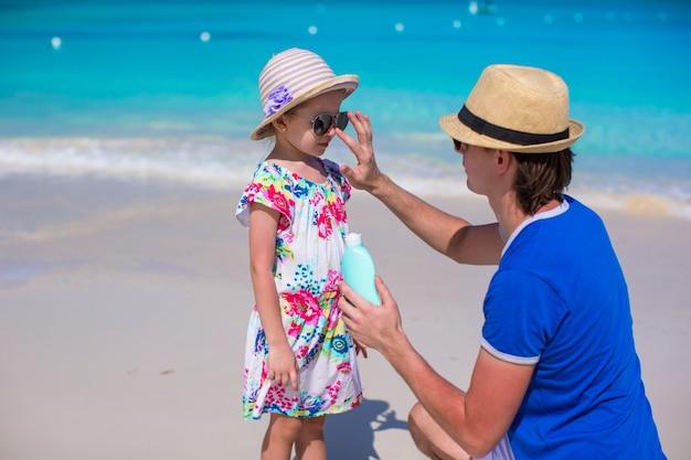 Padre aplica crema de protección solar en la nariz de su pequeña hija
