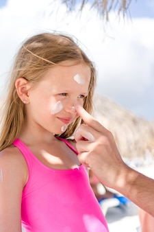 Padre aplicando crema solar a la nariz de la hija