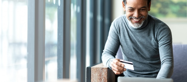 Padre asiático del inconformista barbudo atractivo o viejo hombre hispánico que usa el pago del ordenador portátil y de la tarjeta de crédito