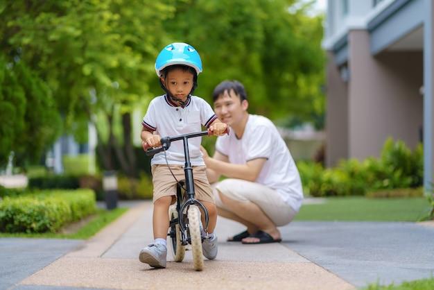 Padre asiático que enseña a su hijo a andar en bicicleta en el jardín de un vecindario, los padres interactúan con sus hijos durante todo el día.
