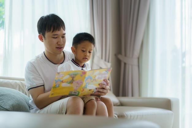 Padre asiático sostiene un libro para enseñar a sus hijos a leer en el sofá de la sala de estar, los padres interactúan con sus hijos durante todo el día.