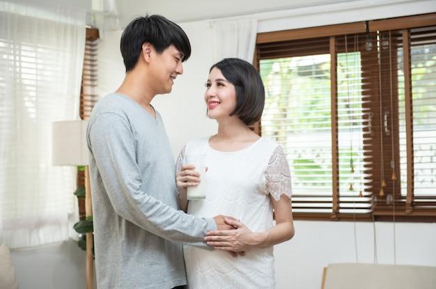 Padre asiático stand lado mirar mujer embarazada con sonrisa