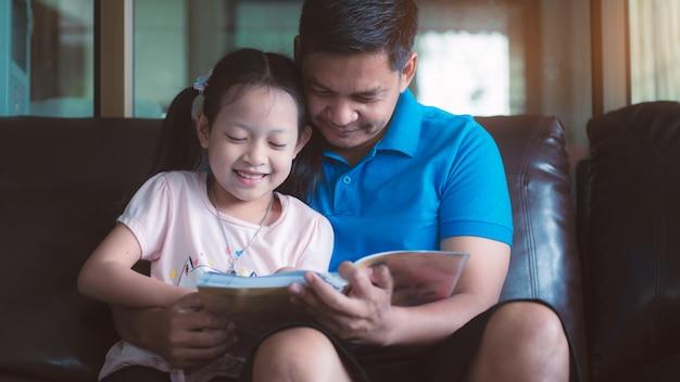 Padre asiático y su hija leyendo un libro en casa