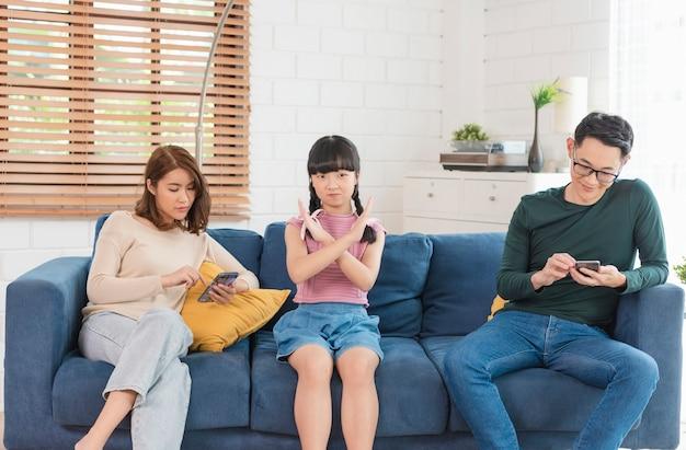 Padre asiático con tableta y teléfonos móviles en casa. adicto a los dispositivos, dependencia de gadgets por uso excesivo.