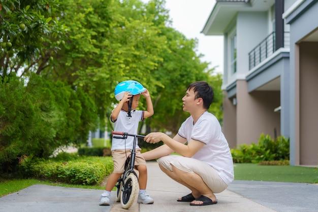 Padre asiático usa un casco para su hijo mientras le enseña a su hijo a andar en bicicleta en un jardín del vecindario, los padres interactúan con sus hijos durante todo el día.