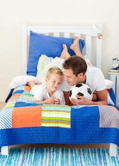 Padre atractivo y su hijo jugando con un balón de fútbol