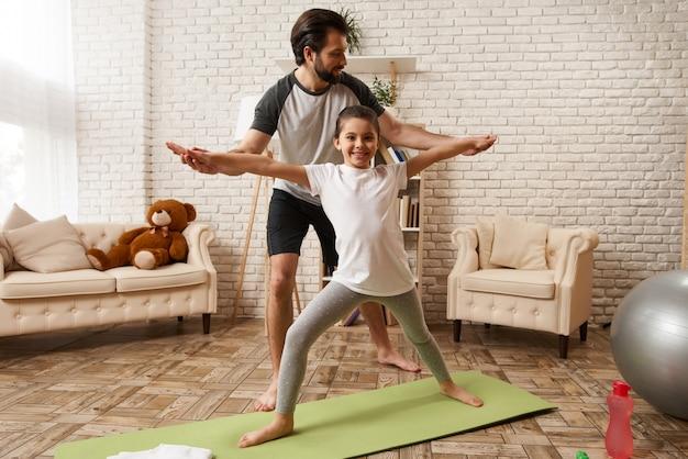El padre ayuda a la hija a corregir la postura en casa.