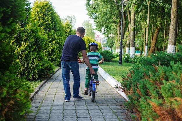 Padre ayuda hijo a andar en bicicleta en el parque de verano. vista trasera