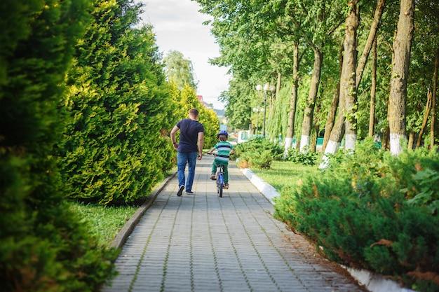 Padre ayuda hijo a andar en bicicleta en el parque de verano.