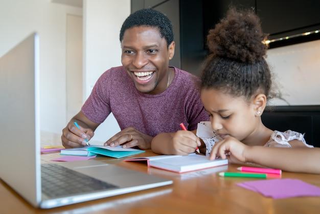 Padre ayudando y apoyando a su hija con la escuela en línea mientras se queda en casa