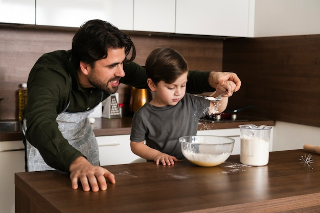Padre ayudando a hijo a hacer masa