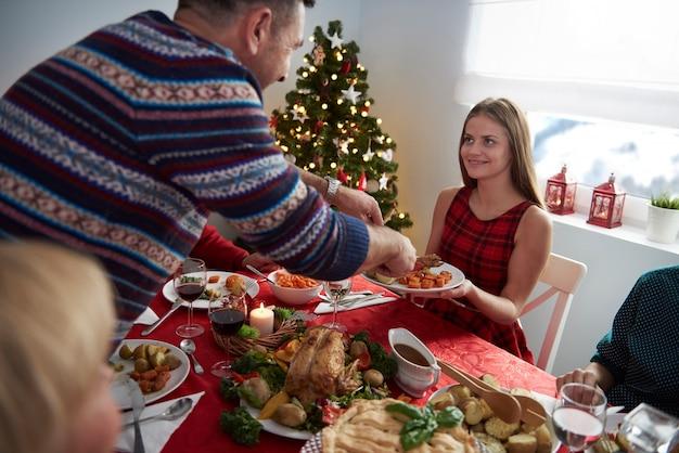 Padre ayudando a su hija en la víspera de navidad