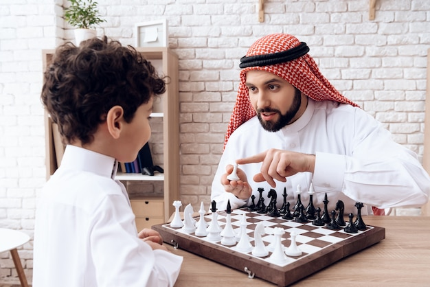 El padre barbudo árabe y el pequeño hijo juegan al ajedrez.