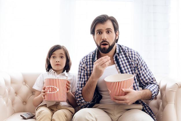 Padre barbudo con un hijo pequeño está viendo una película emocionante.