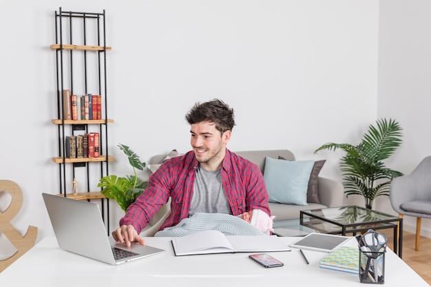 Padre, con, bebé, usar la computadora portátil, en el escritorio