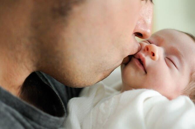 Padre besando a su bebé recién nacido.