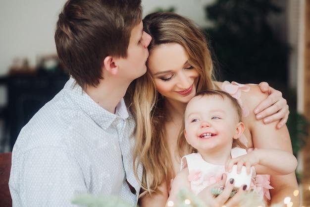 Padre besando a la bella mujer rubia, que sostiene en las manos pequeña hija linda.